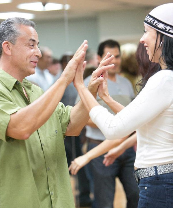 man and woman happily dancing in a salsa class
