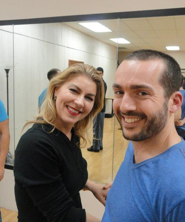 man and woman smiling and dancing during Bachata class